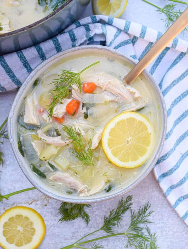 Bowl of Whole30 Greek Lemon Chicken Soup with slices of lemon and fresh dill sprigs
