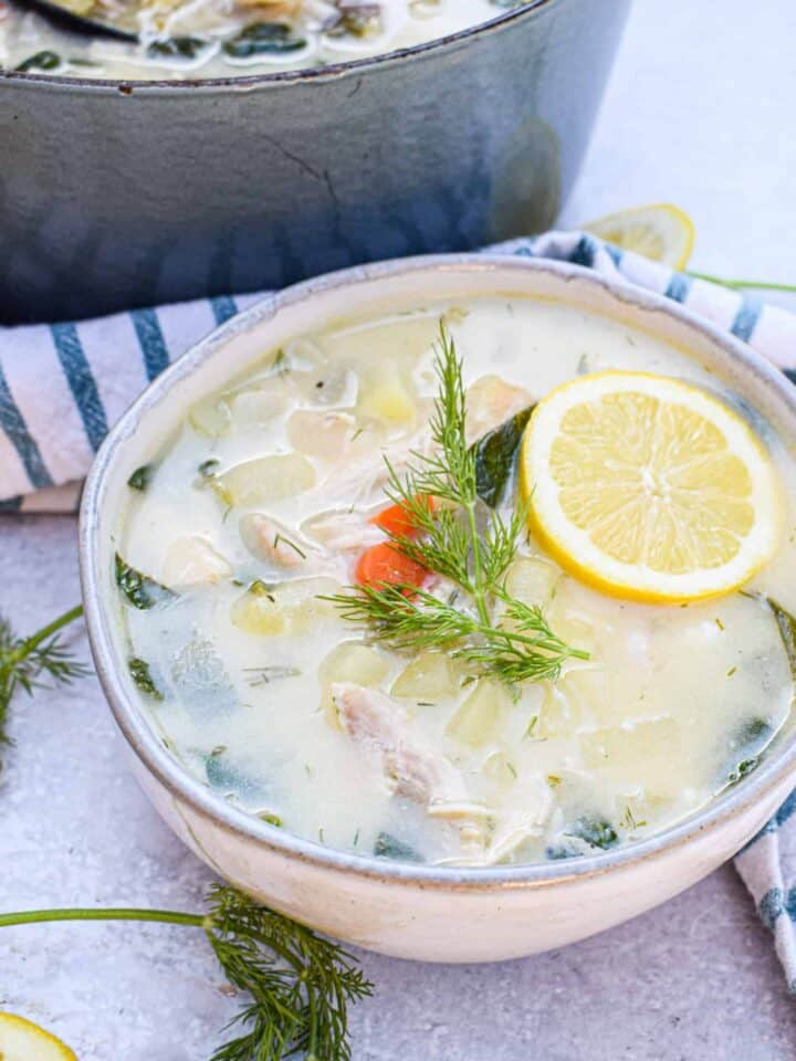 bowl of Whole30 Greek Lemon Chicken Soup with slice of lemon and fresh dill