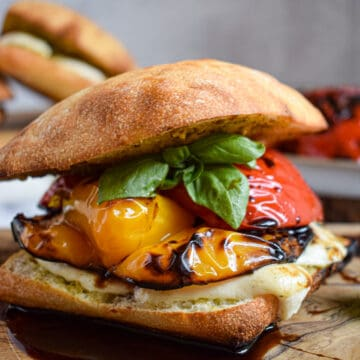 Grilled bell pepper and mozzarella sandwich with aged balsamic, pesto and bail on ciabatta bun. vegetarian summer dinner