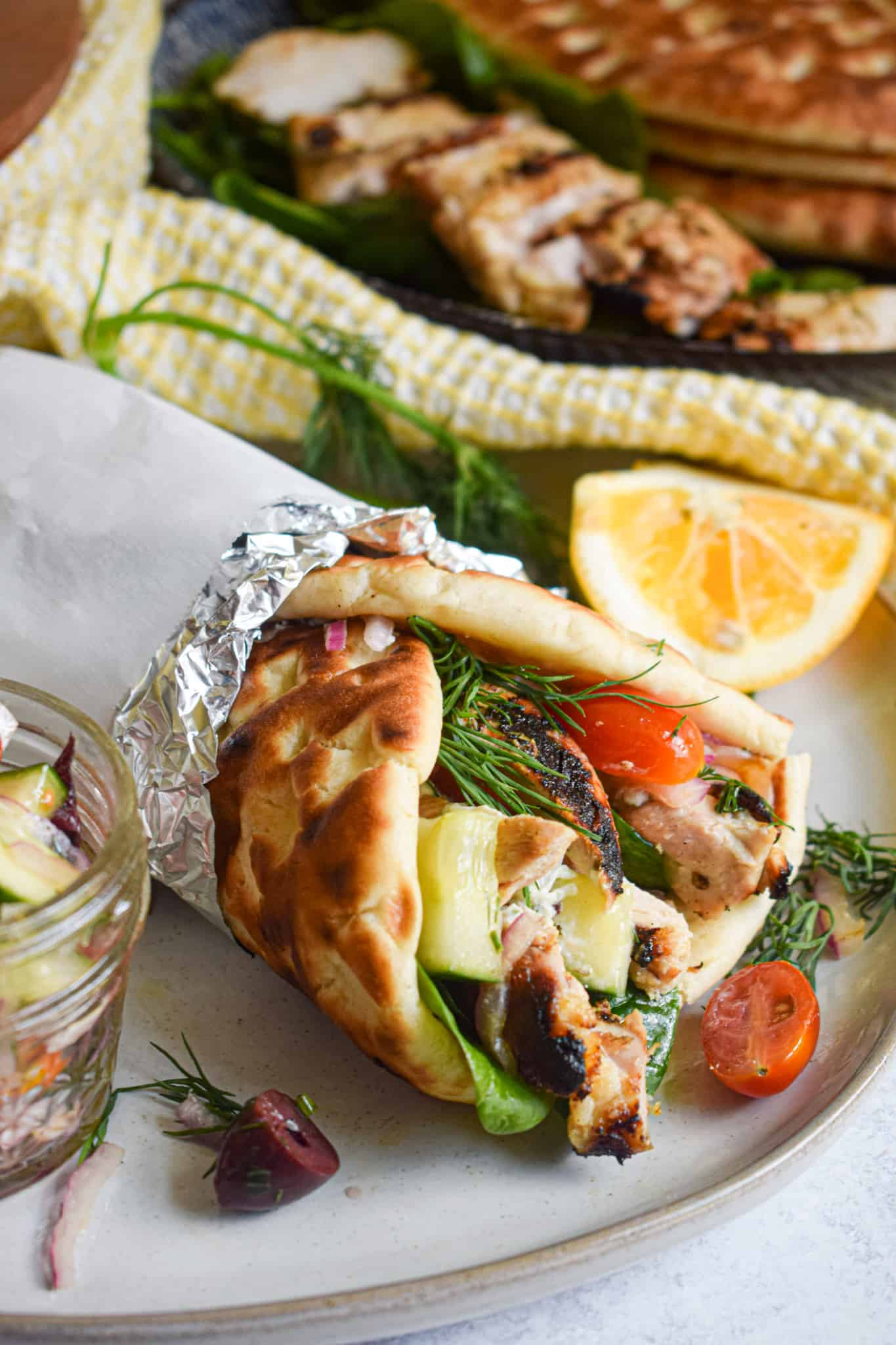 Grilled Greek Chicken Gyros with cucumbers tomatoes spinach dill and tzatziki