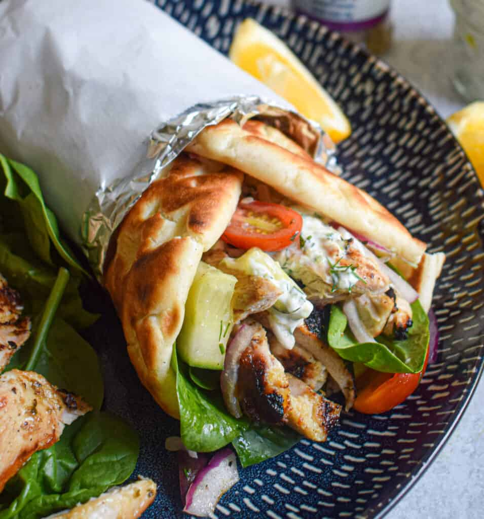 Grilled greek chicken gyro with tzatziki and cucumber salad and fresh herbs