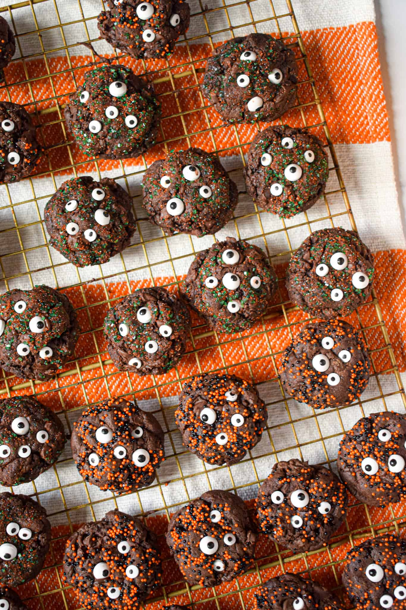 spooky chocolate cookies for halloween with candy eyeballs and sprinkles