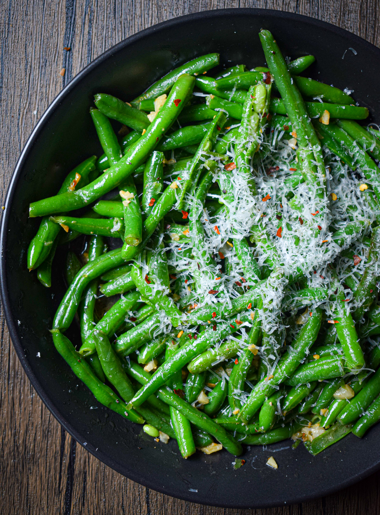 sauteed green beans with garlic and butter topped with parmesan cheese and red pepper flakes